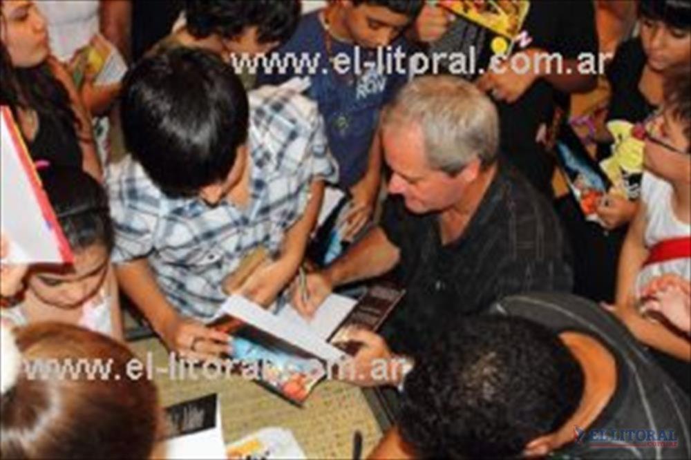 El autor firma ejemplares y los dedica a los chicos que se acercaron a escucharlo en la Feria del Libro Chaqueño y Regional.