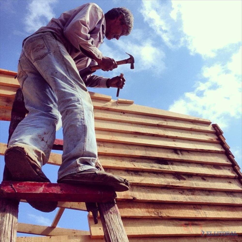 TRABAJO. Los vecinos colaboran con los voluntarios para la construcción de las viviendas de madera.